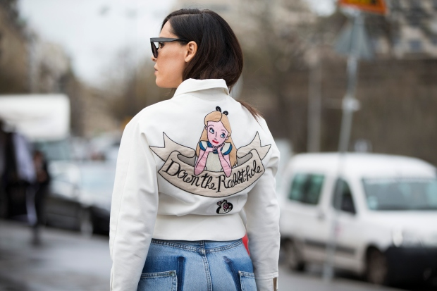 "PARIS, FRANCE - JANUARY 27: Evangelie Smyrniotaki wears an Olympia Le Tan ropped white zipped jacket with prints and ""Down the Rabbit Hole"" princess print and Vetements jeans at the Elie Saab Couture show at Trocadero on January 27, 2016 in Paris, France. (Photo by Melodie Jeng/Getty Images)"